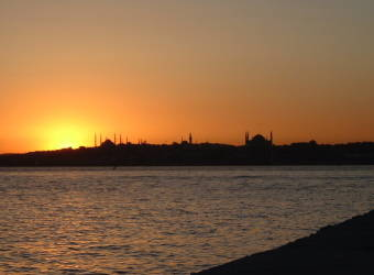 View across the Bosphorus in Istanbul to the Sultanahmet district: Sunset behind the Blue Mosque and the Aya Sofya or Haghia Sophia.