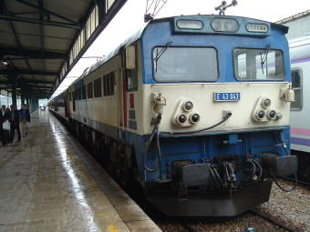 Blue and white locomotive pulling a Turkish passenger train.